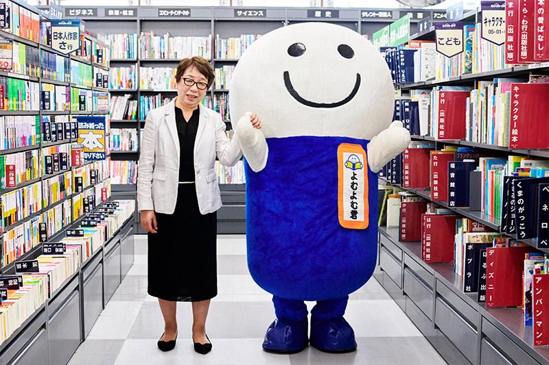 店舗で微笑む橋本真由美さんとよむよむ君