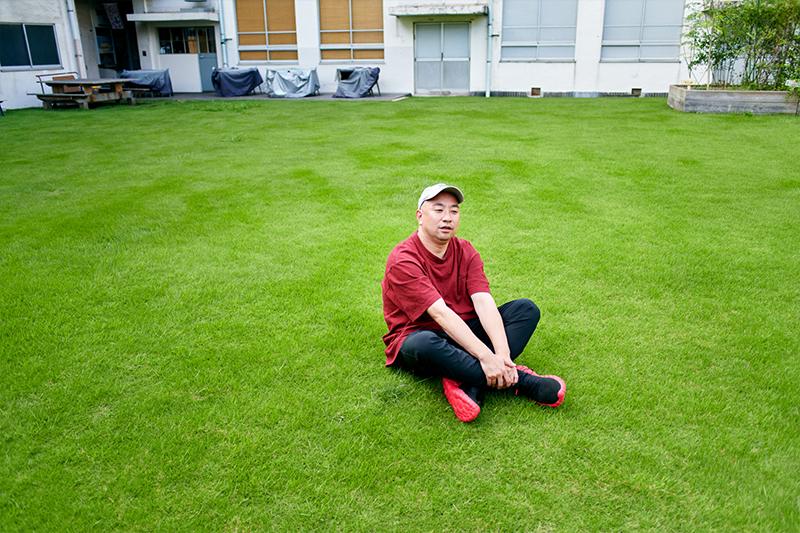 芝生に座るレイザーラモンRGさん