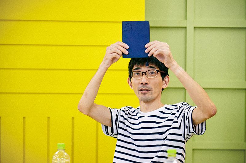 ブックオフのブックカバーを見せる佐藤さん