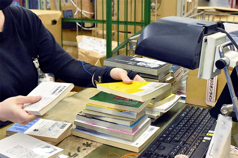 ブックオフの倉庫で査定する女性