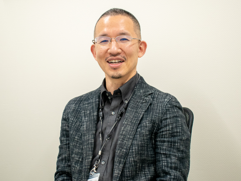 笑顔でカメラを見つめる、店舗開発部の平野紘司さん