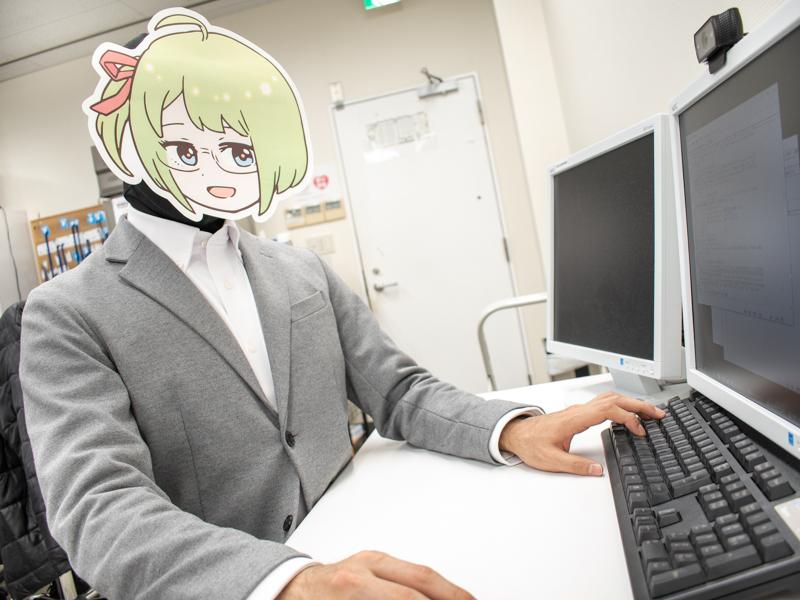 パソコンの前に座りコーディングをするミヤザワさん
