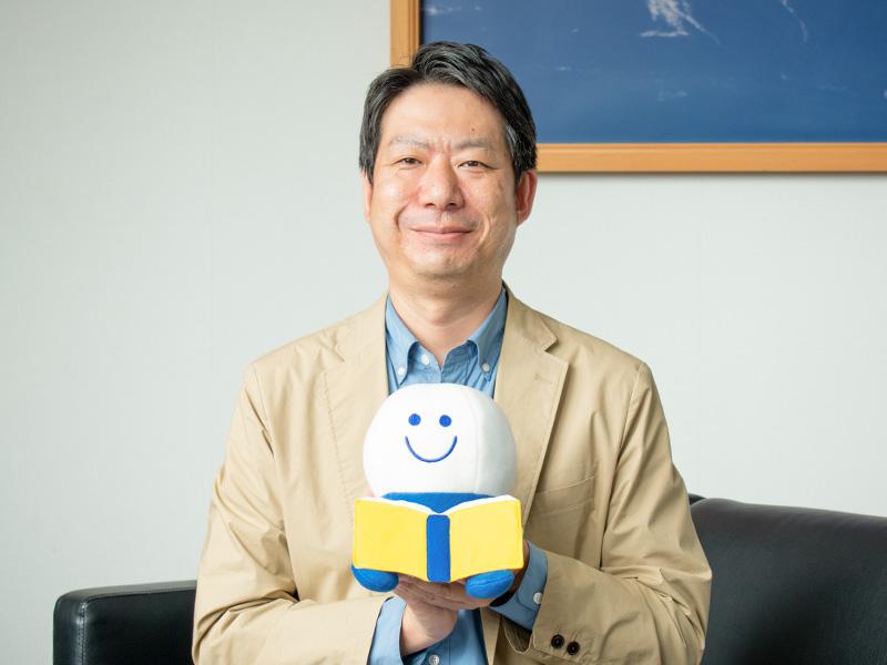 よむよむ君人形を持ってほほ笑む千田竜也さん