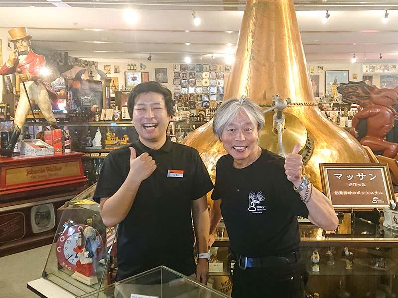 名物ポットスチルの前でサムズアップしている橋本成房さんと高嶋甲子郎さん。